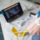 Zu sehen ist ein CO2-Monitor zur Schlafüberwachung, im Vordergrund eine Hand, an der ein Sensor angeschlossen ist.