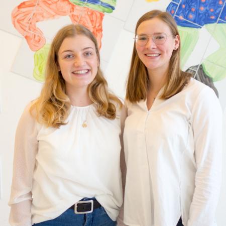 Zwei Schülerinnen, die das Projekt mit geleitet haben, lächeln in die Kamera bei der symbolischen Spendneübergabe in der Tübinger Uni-Kinderklinik.