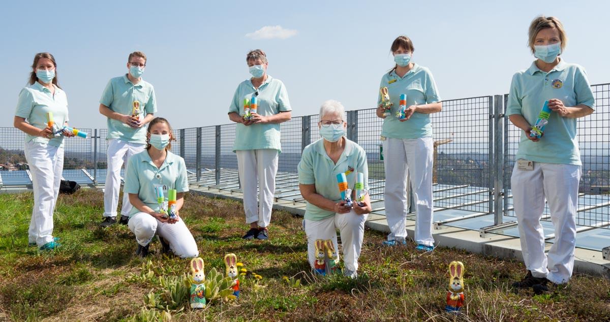Das Erzieherinnen-Team steht auf dem Balkon der Kinderklinik und zeigt die Schokohasen und Geschenke für die Patienten der Kinderklinik Tübingen.