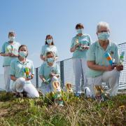 Die Erzieherinnen zeigen auf dem Balkon der Kinderklinik die Geschenke zu Ostern